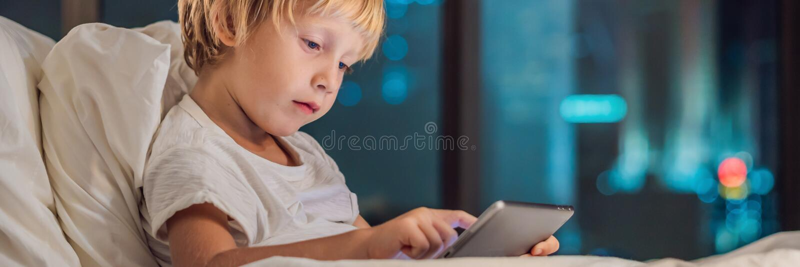 男孩在他的床在夜城市的背景使用片剂在去前睡 孩子和技术概念横幅, 库存图片