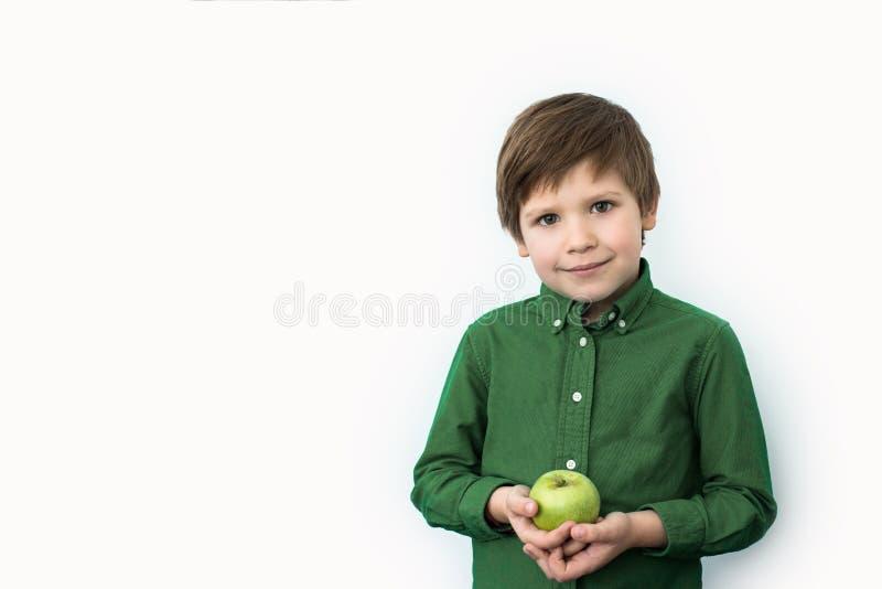 男孩在他的手,情感上拿着一个绿色苹果 免版税库存照片