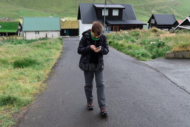男孩在使用与智能手机的法罗群岛附近走 免版税库存照片