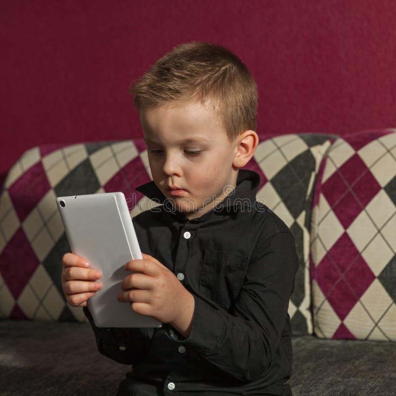 男孩在使用在片剂的长沙发的客厅 免版税库存图片