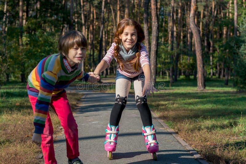 男孩在公园帮助女孩路辗冰鞋 兄弟支持 免版税库存图片