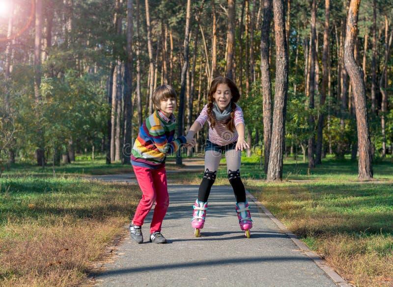 男孩在公园帮助女孩路辗冰鞋 兄弟支持 免版税库存照片