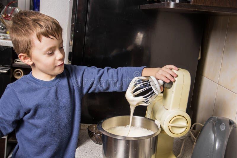 男孩在厨房揉杯形蛋糕的面团在搅拌器,增加成份 免版税库存照片