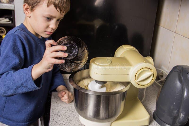 男孩在厨房揉杯形蛋糕的面团在搅拌器,增加成份 库存照片