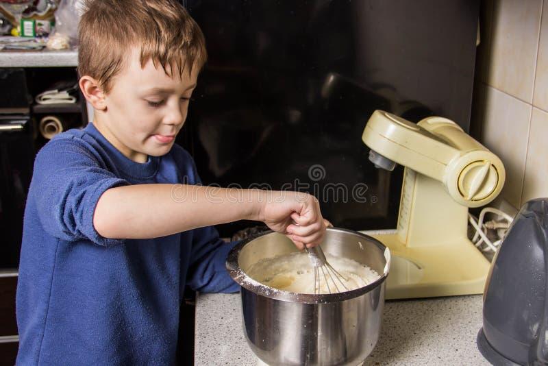 男孩在厨房揉杯形蛋糕的面团在搅拌器,增加成份 库存图片