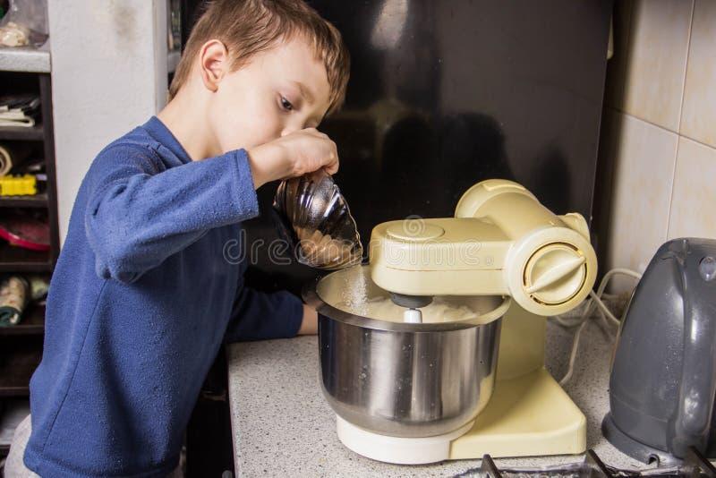 男孩在厨房揉杯形蛋糕的面团在搅拌器,增加成份 免版税库存图片