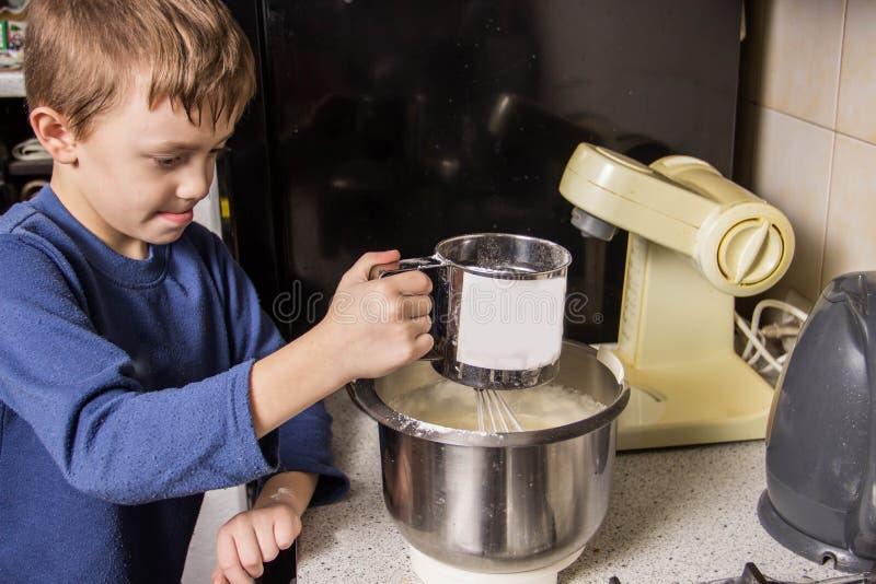 男孩在厨房揉杯形蛋糕的面团在搅拌器,增加成份 图库摄影