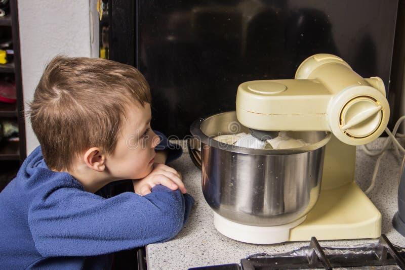 男孩在厨房揉杯形蛋糕的面团在搅拌器,增加成份 免版税图库摄影