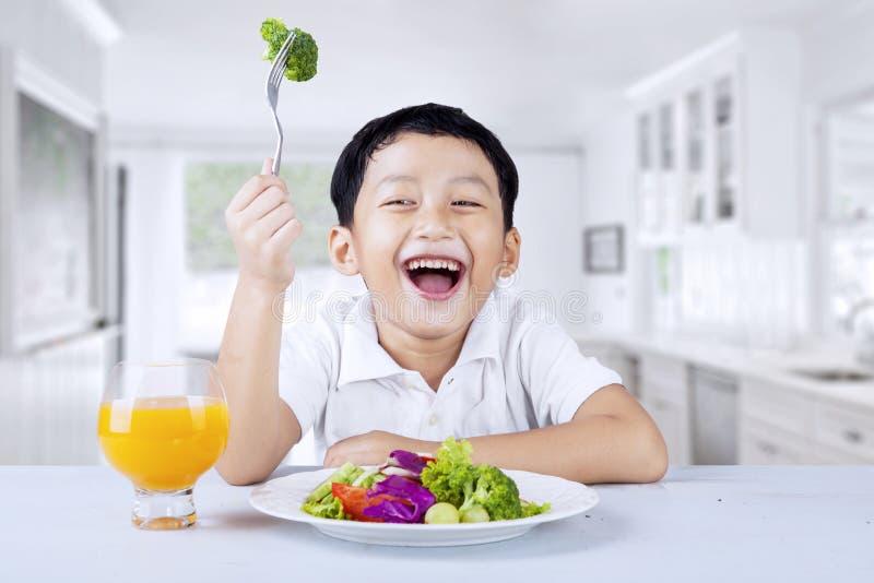 男孩在厨房里吃菜沙拉 免版税图库摄影