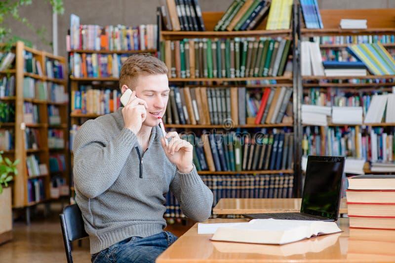 男孩在图书馆里谈话在电话 免版税库存照片