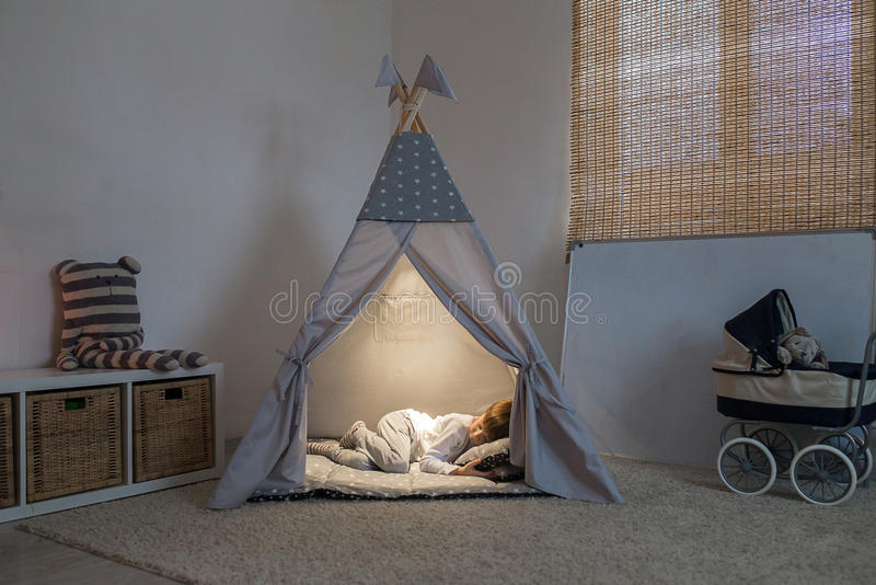 男孩在圆锥形帐蓬睡觉 库存照片
