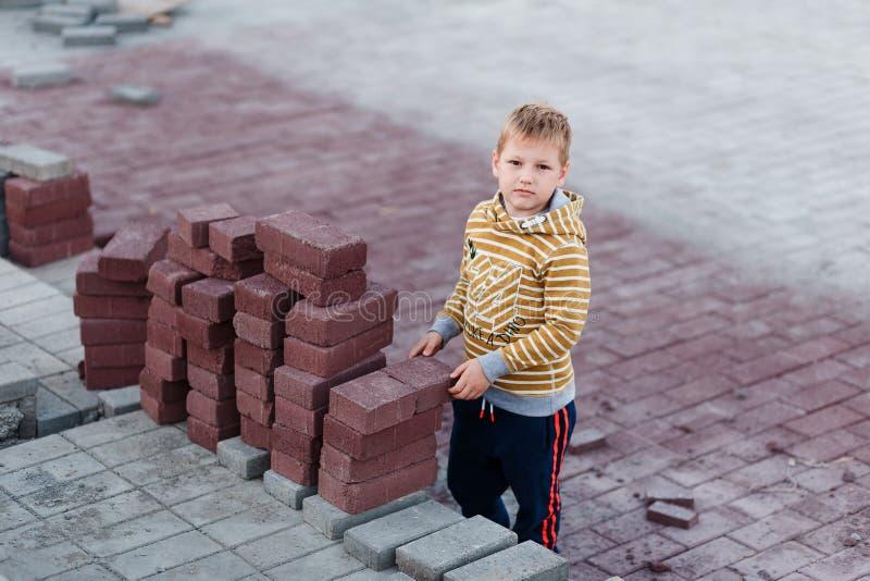 男孩在大厦砖附近站立 放置铺路板 孩子和行业 免版税库存图片