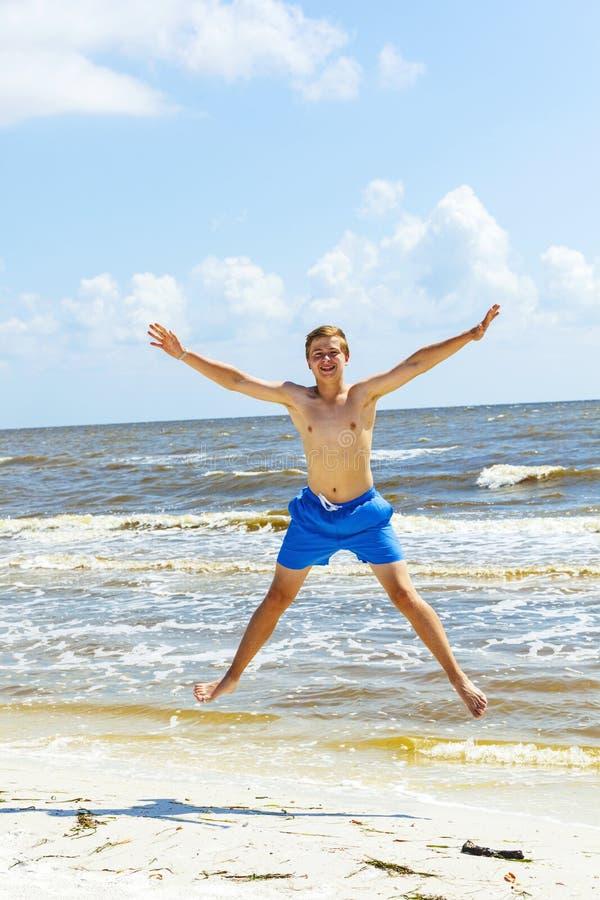 男孩在天空中跳在海滩 免版税库存图片