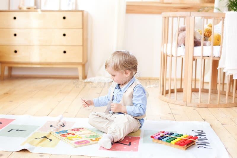 男孩在家使用与木玩具 孩子的教育木玩具 男孩的画象坐在孩子的地板 库存照片