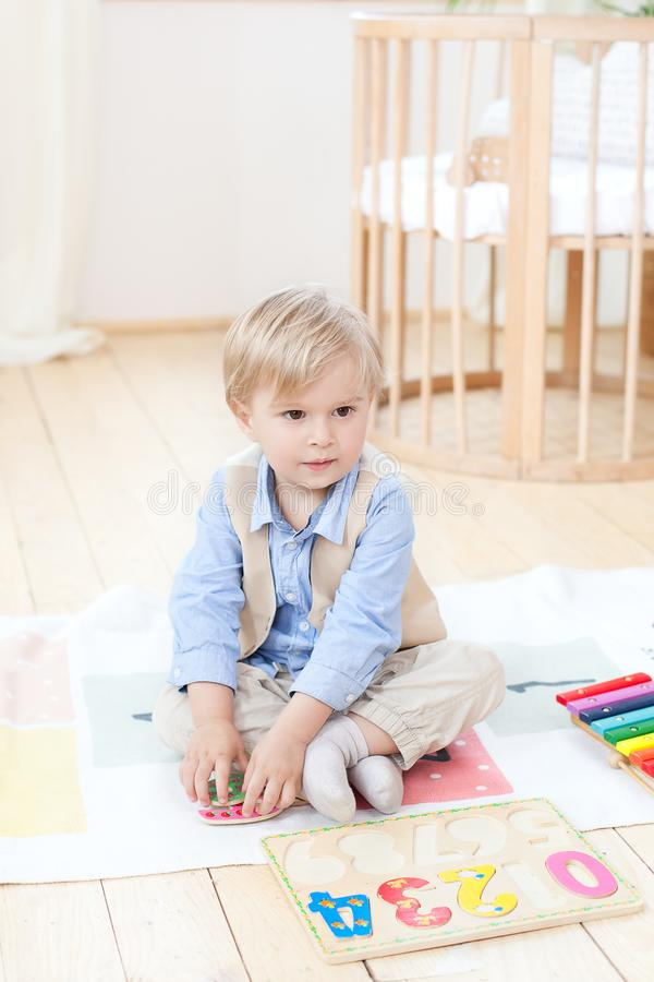 男孩在家使用与木玩具 孩子的教育木玩具 男孩的画象坐在孩子的地板 图库摄影