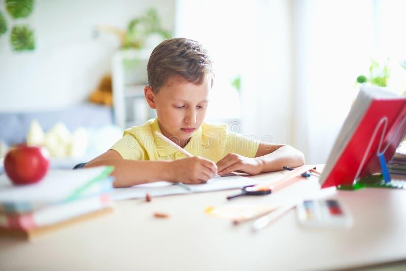 男孩在家做他的家庭作业 愉快的孩子在与学校用品的桌上集中了在撤退的文字,做 库存照片