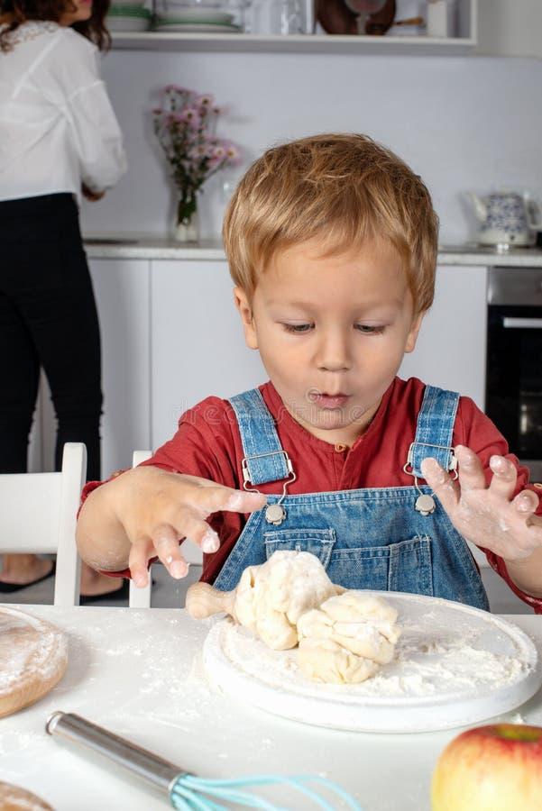 男孩在家揉在厨房用桌上的面团以欢欣 库存图片