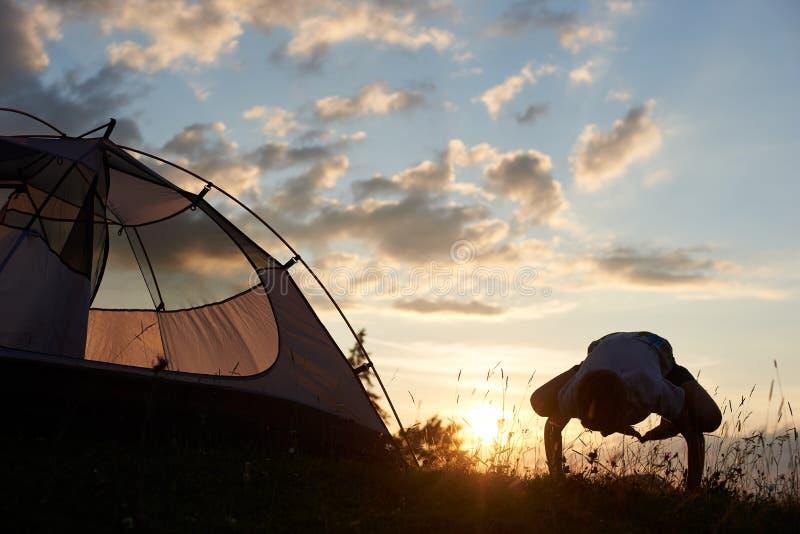 男孩在山顶部实践瑜伽在帐篷附近在黎明在与云彩的蓝天下 免版税库存图片