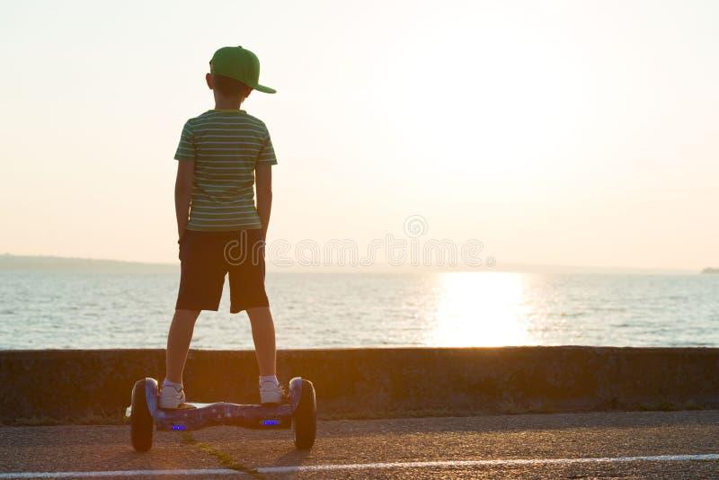 男孩在平衡板乘坐 E 库存照片