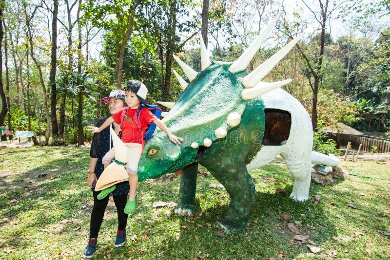 男孩在恐龙雕象附近坐 免版税库存图片