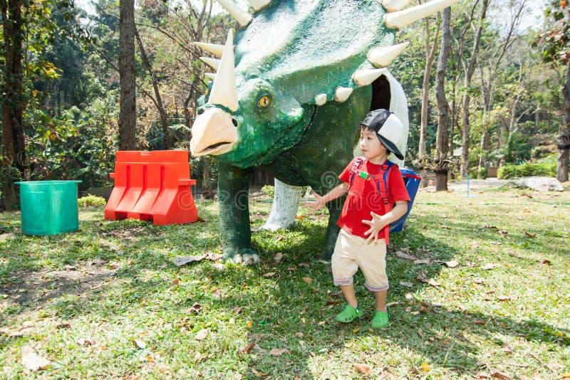 男孩在恐龙雕象附近走 库存图片