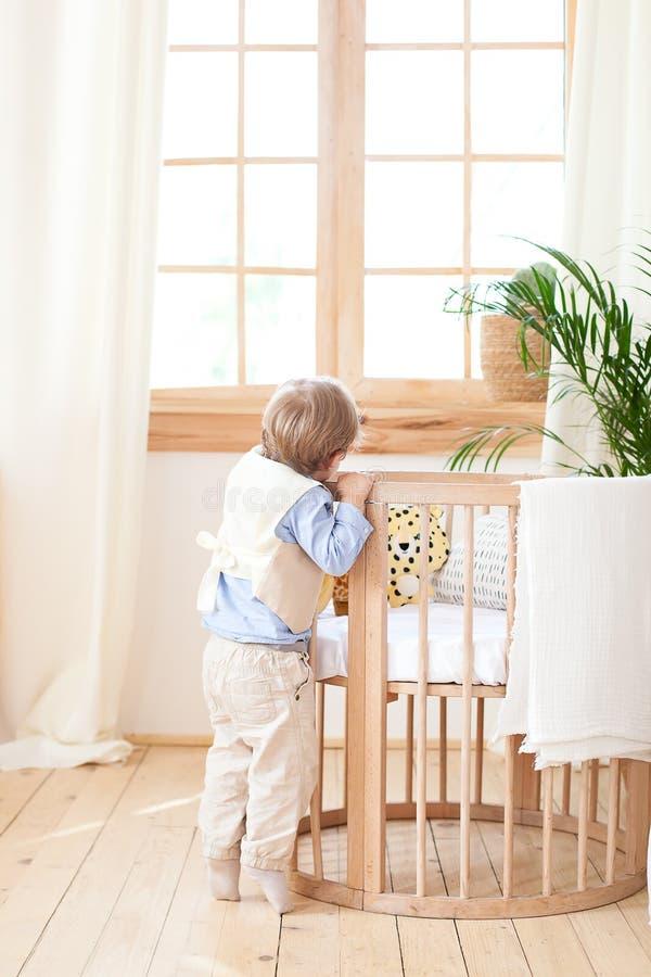 男孩在托儿所和偷看的轻便小床旁边站立 孤独的婴孩在幼儿园在小儿床附近 ?? 环境友好的ch 图库摄影