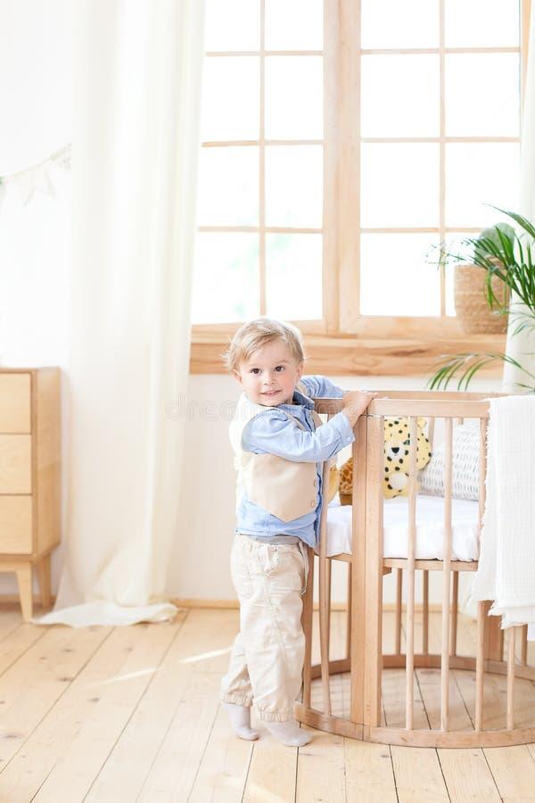 男孩在托儿所站立单独在一个轻便小床旁边 孤独的婴孩在幼儿园在小儿床附近 ?? 环境友好的孩子的 库存图片