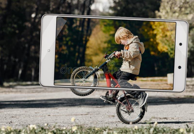 男孩在智能手机的框架的骑马自行车 免版税库存图片