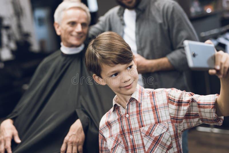 男孩在有两个更老的人的一个智能手机做selfie在理发店 免版税库存图片