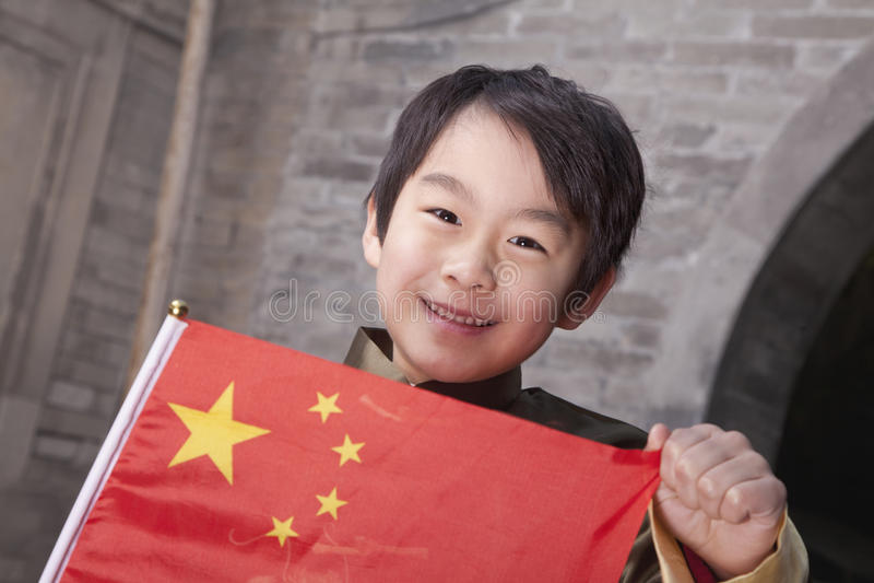 年轻男孩在有中国旗子的传统庭院里 免版税库存图片