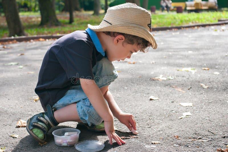 男孩在有白垩的路画 免版税库存图片