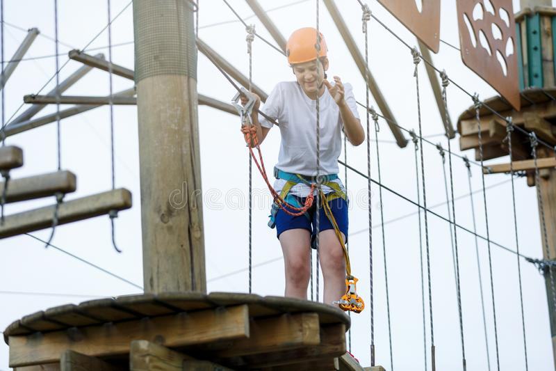 男孩在森林冒险公园 在橙色盔甲的孩子和在高绳索足迹的白色T恤杉攀登 上升室外,娱乐中心 免版税库存图片