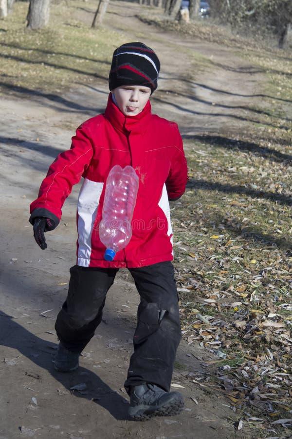 男孩在森林秋天的演奏橄榄球争斗 图库摄影