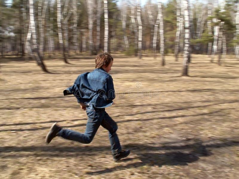 男孩在森林里跑 免版税库存图片
