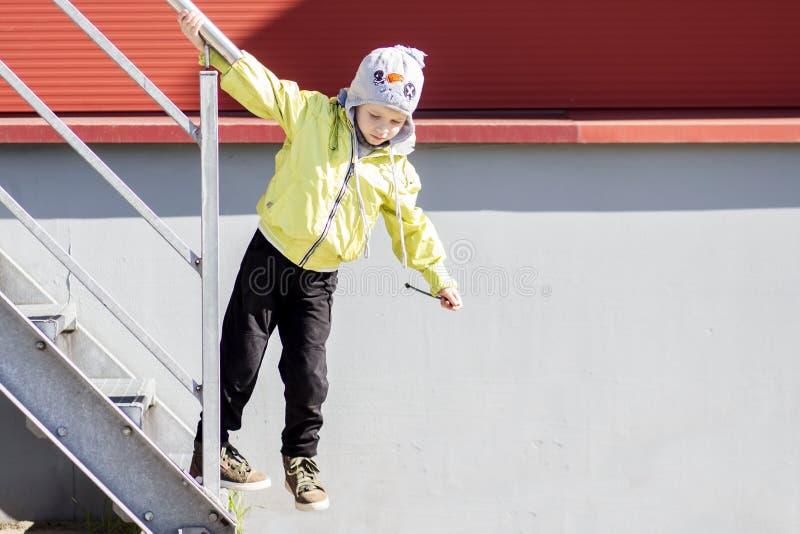 男孩在楼梯栏杆举行并且垂悬在城市处所庭院里  孩子街道生活  在街道上的儿童游戏 免版税库存照片