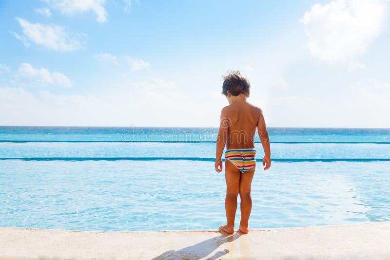 男孩在游泳池的石房客站立 免版税图库摄影