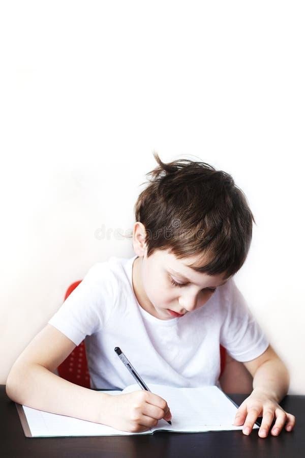 男孩在笔记本坐在桌上并且写 孩子坐并且家庭作业 免版税库存图片