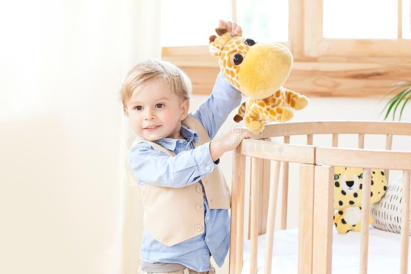 男孩在轻便小床旁边在他的手上站立在托儿所并且拿着一个玩具 孩子是在幼儿园和戏剧 环境友好的池氏 图库摄影