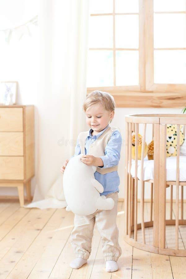 男孩在轻便小床旁边在他的手上站立在托儿所并且拿着一个玩具 孩子是在幼儿园和戏剧 环境友好的池氏 免版税库存图片