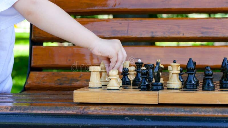 男孩在长凳的棋枰采取行动 免版税库存照片