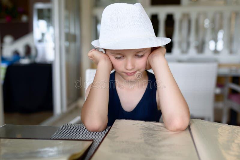 男孩在餐馆或咖啡馆的读书菜单 免版税库存图片