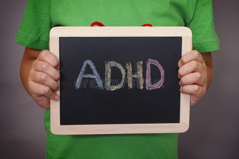 年轻男孩在黑板拿着ADHD文本被写 免版税库存照片