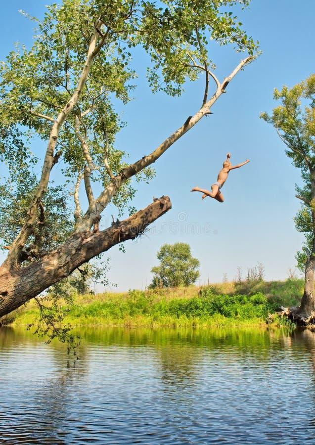 男孩在从树的水中跳 免版税库存图片