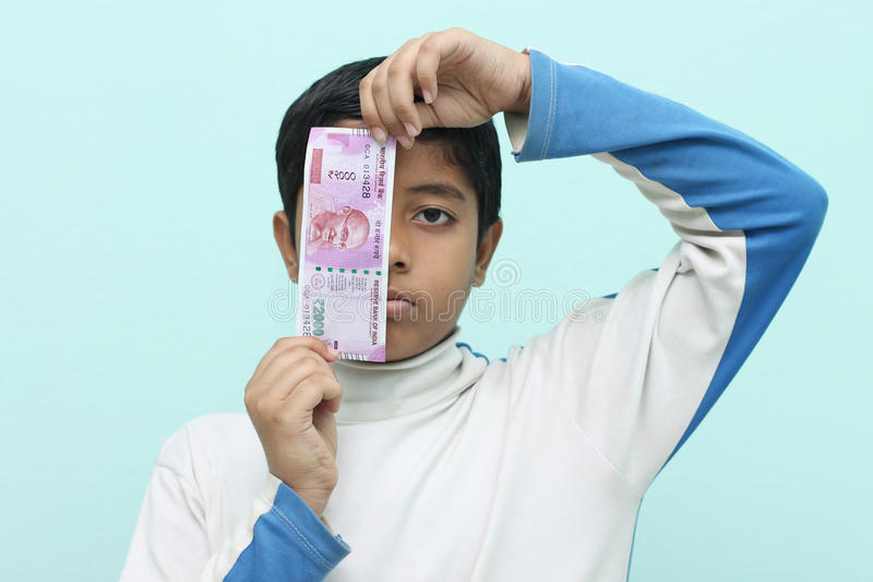 男孩在他的手上的拿着2000卢比新的印地安金钱 库存照片