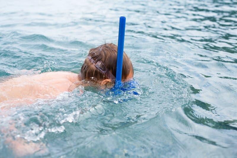 男孩在戴着佩戴水肺的潜水的海一个面具。 免版税图库摄影