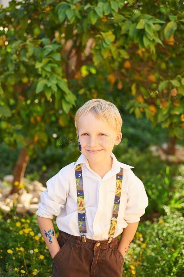 男孩在绿色庭院里 库存照片