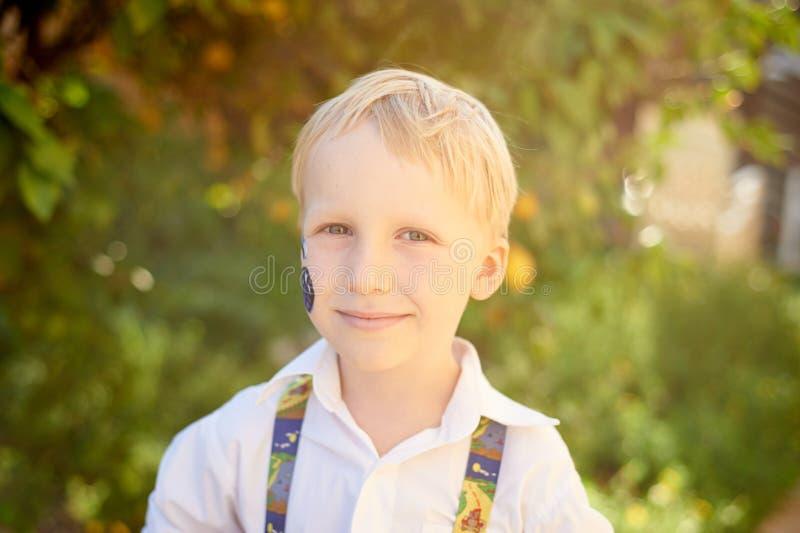 男孩在绿色庭院里 库存图片