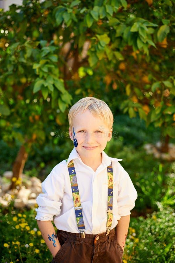男孩在绿色庭院里 免版税图库摄影