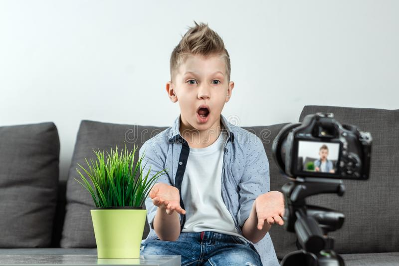 男孩在SLR照相机,特写镜头前面坐 博客作者,写博克,技术,在互联网上的收入 r 库存照片