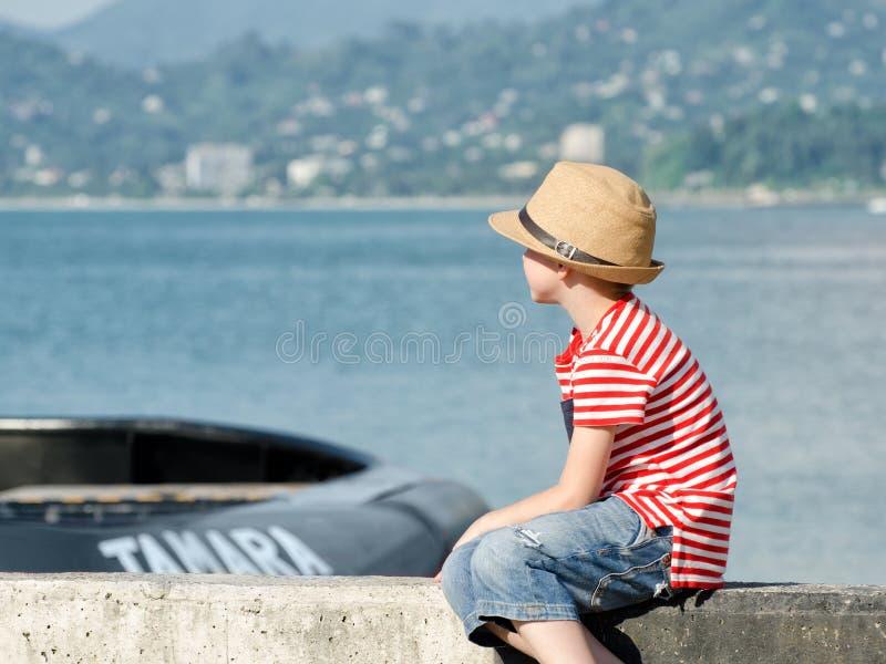 男孩坐与帽子和镶边T恤杉的海滩,看船 侧视图 免版税图库摄影